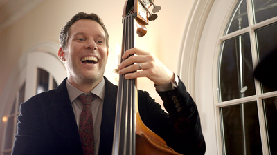 Alegria male upright bass player performing live for guests in a ballroom