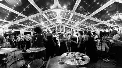 Another Level female guests dancing under a tent at an outdoor wedding reception