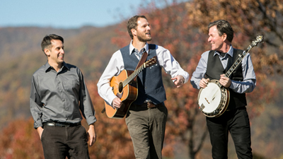 Bent Mountain Trio promotional photo formal while laughing and carrying guitar and banjo