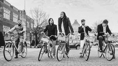 Dickens The promotional photo of band riding bikes in a city
