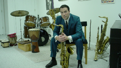 Jeff Decker Band promotional photo of male saxophone player holding a sax