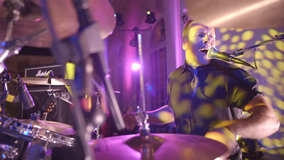 OnLive drummer performs and sings in a ballroom