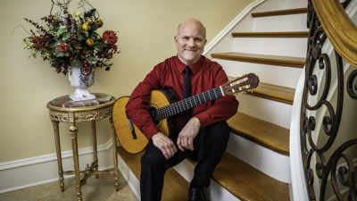 Peter Richardson promotional photo with guitar seated at the bottom of a staircase