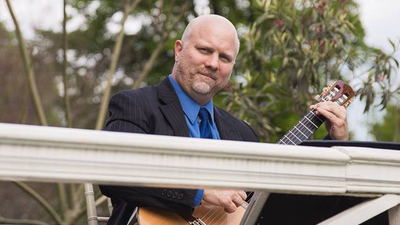 Peter Richardson live guitar performance at an outdoor concert