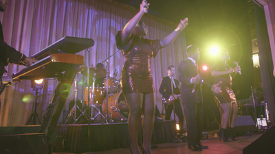 Queen City Band band sings and dances on stage at country club