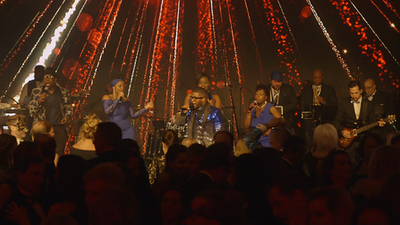 Queen City Band entire band plays music on stage at large venue