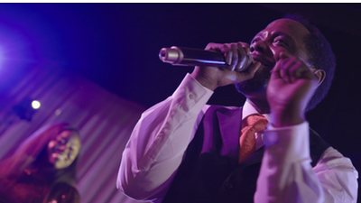 Queen City Band male singer on stage singing for a corporate event party