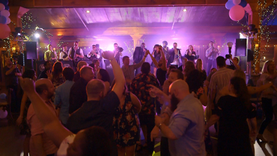 Revel Arcade guests dance and band plays on stage in barn