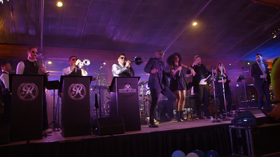 Revel Arcade band singing and dancing on stage for live performance at a private event