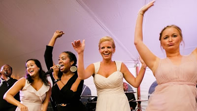 Soul Expressions bridesmaids dance with lead female singer on stage at reception