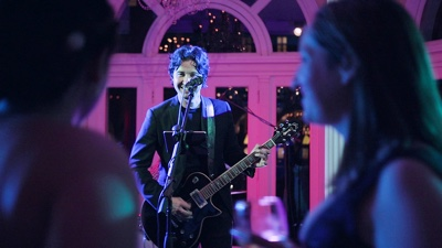 Finns The solo male guitar player performing for guests in a ballroom