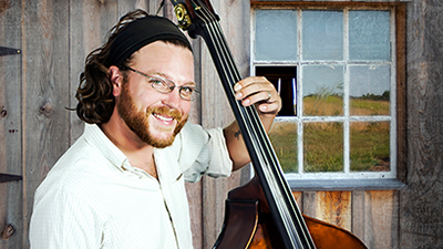 Whiskey Rebellion The promotional photo of male bass player outside at a farm